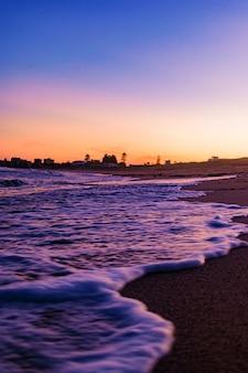 Piękne ujęcie scenerii zachodu słońca na plaży przy bezchmurnym niebie