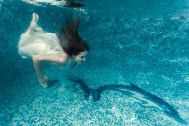 Piękne ujęcie seksownej kobiety w białym suknie, nurkującej pod wodą w basenie
