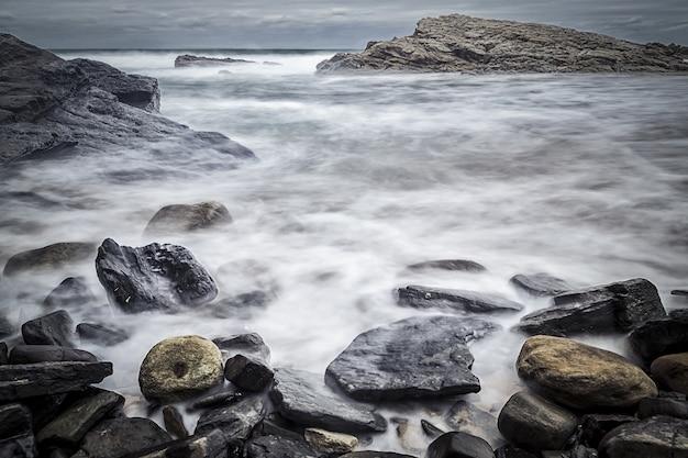 Piękne ujęcie skał na brzegu morza z ponurym niebem