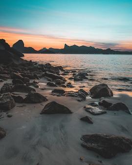 Piękne ujęcie skalistego wybrzeża morza o zachodzie słońca z niesamowitym błękitnym niebem