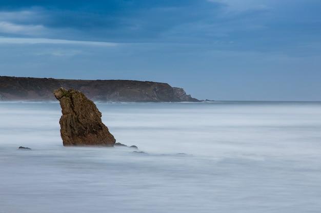 Piękne ujęcie skały wystającej z wody w morzu