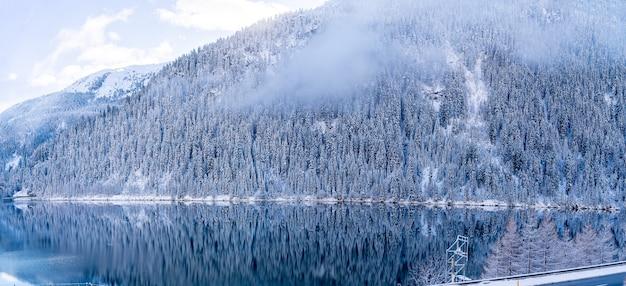 Piękne ujęcie spokojnego jeziora z zalesionymi górami pokrytymi śniegiem po bokach