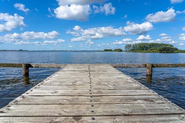 Piękne ujęcie starego drewnianego pomostu wykonanego z desek pod błękitnym pochmurnym niebem