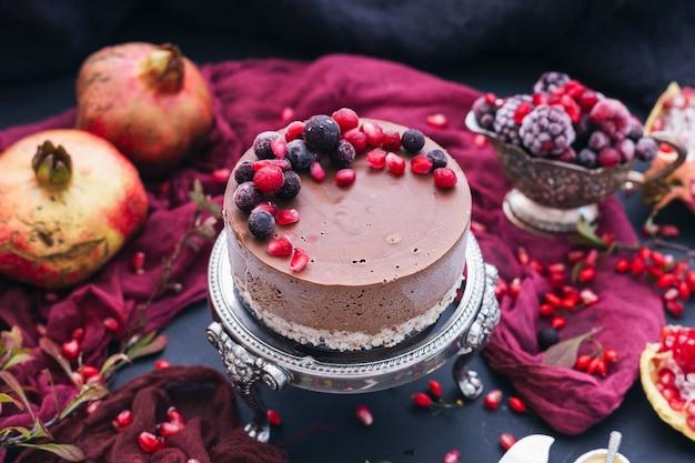 Piękne ujęcie surowego wegańskiego ciasta z rozrzuconymi po całym terenie jagodami i pestkami granatu