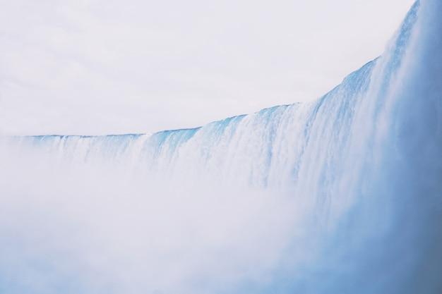Piękne ujęcie szerokiego dużego wodospadu z niesamowitym jasnym niebem w tle
