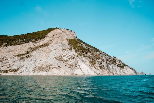 Piękne ujęcie tropikalnej wyspy otoczonej czystą wodą w słoneczny dzień
