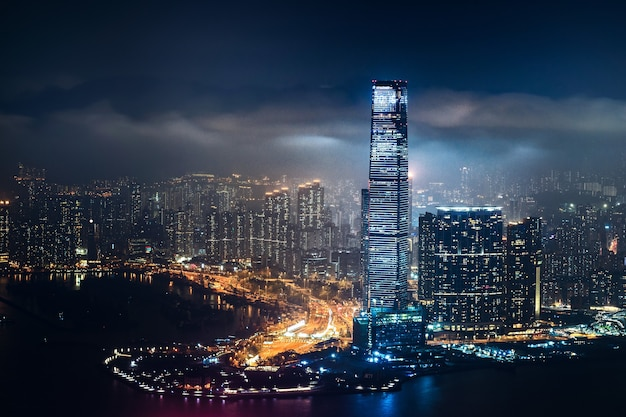 Piękne ujęcie wysokich budynków miejskich pod zachmurzonym niebem w nocy
