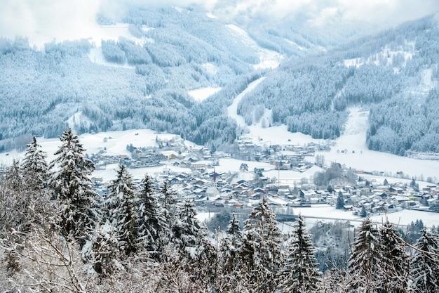 Piękne ujęcie z lotu ptaka zalesionych gór pokrytych śniegiem w ciągu dnia