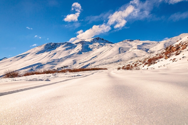 Piękne ujęcie z niskiego kąta zapierającej dech w piersiach górskiej scenerii pokrytej śniegiem w andach cordillera