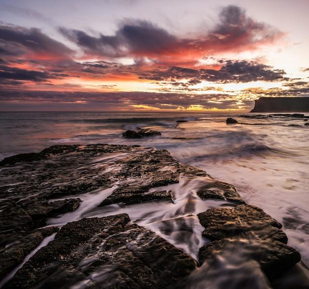 Piękne ujęcie zachodu słońca z kolorowymi chmurami nad morzem