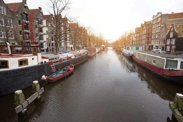 Piękne uliczki, kanał i dom na wodzie w słynnym mieście amsterdam w holandii