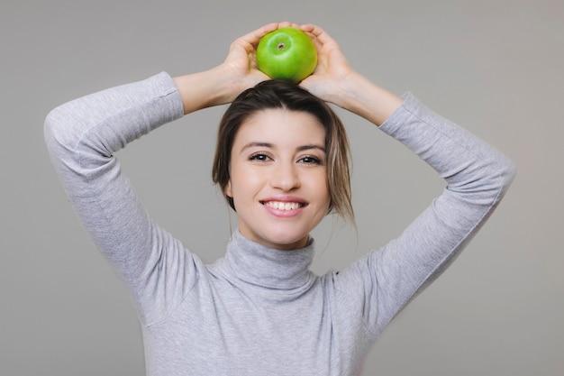 Piękne urocze wesołe panienki w bluzce trzymając świeże zielone jabłko na głowie na szaro