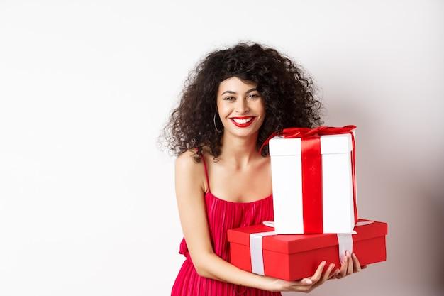 Piękne urodziny dziewczyna z kręconymi włosami, trzymając prezenty urodzinowe i uśmiechając się szczęśliwy, świętuje, stojąc na białym tle.