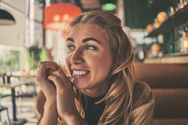 Piękne, uśmiechnięte dziewczyny siedzą w kawiarni
