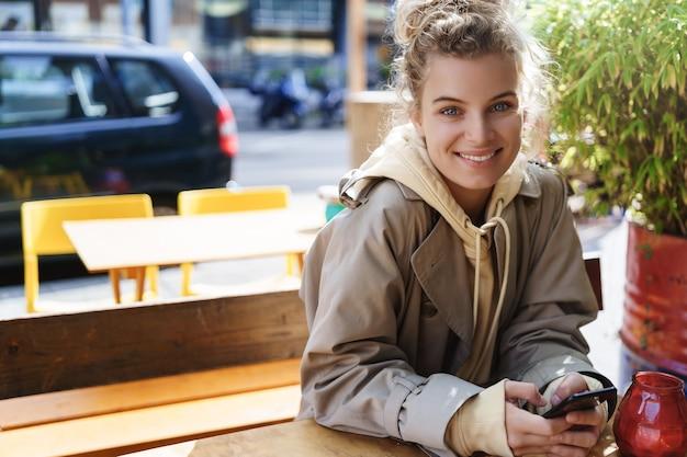 Piękne, uśmiechnięte dziewczyny siedzącej w kawiarni na świeżym powietrzu tabeli. kobieta za pomocą telefonu komórkowego w kawiarni.