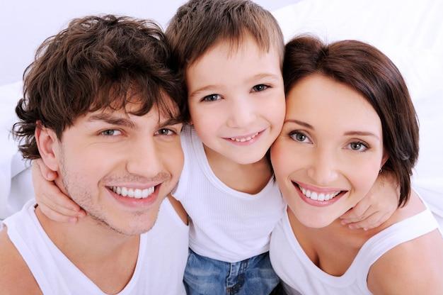 Piękne, uśmiechnięte twarze ludzi. szczęśliwa młoda rodzina złożona z trzech osób