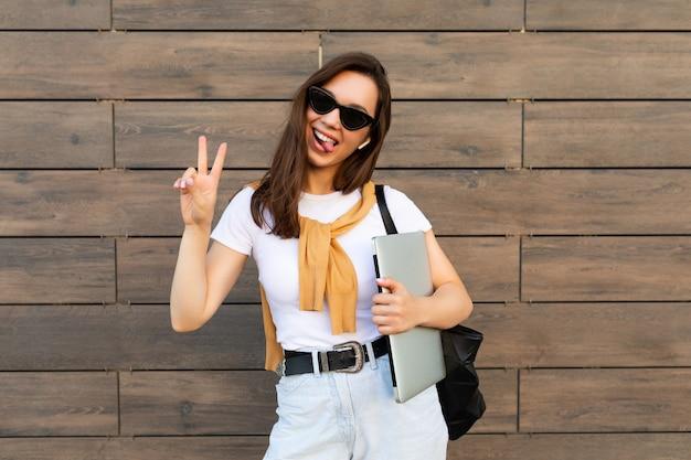 Piękne uśmiechnięte urocze młode kobiety brunet patrząc na kamery posiadania komputera przenośnego i
