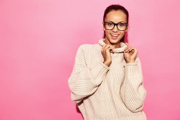 Piękne uśmiechnięte wspaniałe kobiety. kobiety stojące w stylowym białym swetrze na różowej ścianie.