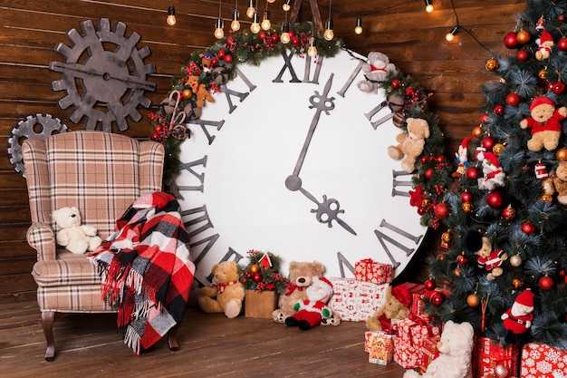 Piękne wakacje urządzone salon z choinką i prezentami. duży magiczny zegar na drewnianej ścianie.