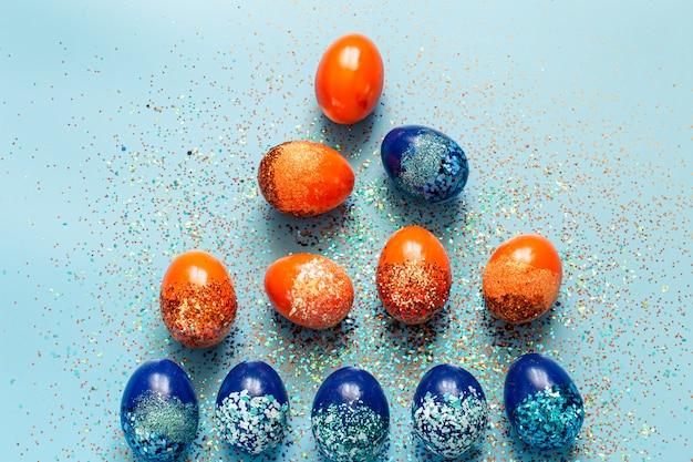 Piękne wielkanocne niebieskie tło z niebieskimi i pomarańczowymi ozdobnymi jajkami.