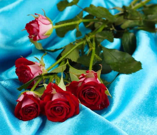 Piękne winne róże na niebieskiej satynie