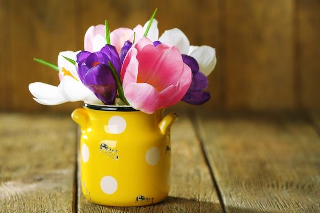 Piękne wiosenne kwiaty w żółtej doniczce na drewnianym tle