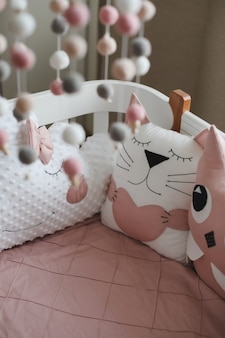 Piękne wnętrze pokoju dziecięcego z łóżeczkiem z poduszkami i różowym kocykiem