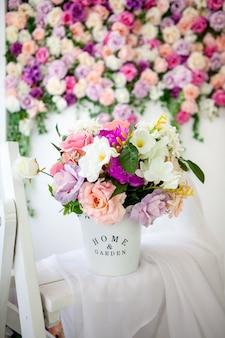 Piękne wnętrze w stylu prowansalskim z jasną ścianą kwiatową, wiaderkiem ze sztucznymi kwiatami