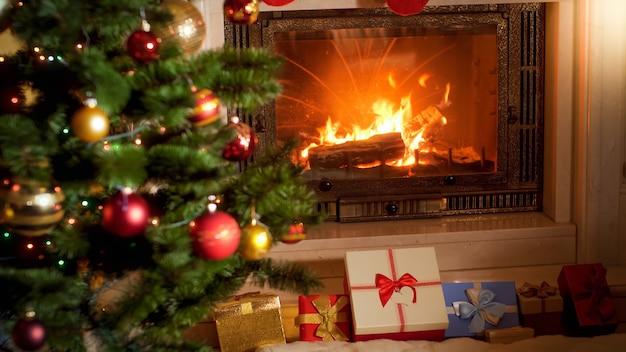 Piękne wnętrze z płonącym kominkiem, choinką i dużym stosem świątecznych prezentów