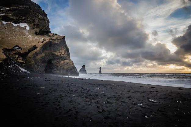 Piękne wybrzeże morza w vik, islandia z zapierającymi dech w piersiach chmurami i skałami na boku