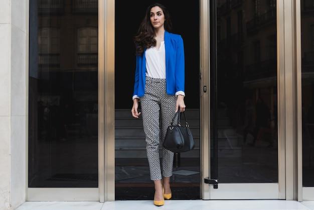 Piękne wykonawczy z niebieską kurtkę i czarną torebką