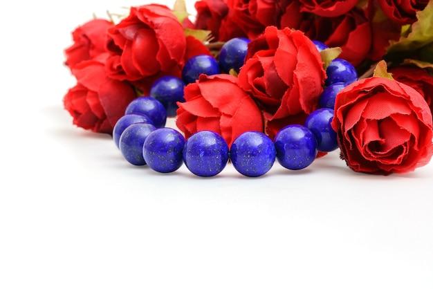 Piękne, wysokiej jakości, błękitne koraliki lapis lazuli w bransoletce z czerwonymi różami na białym tle
