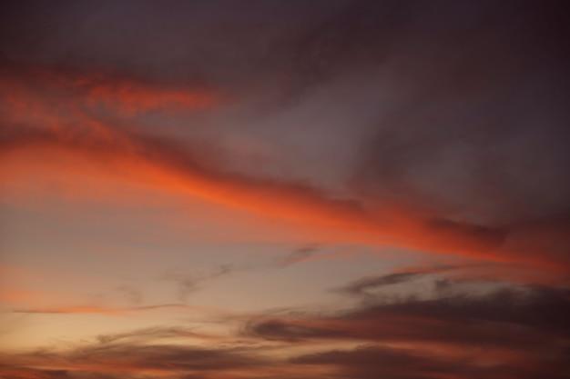 Piękne zachmurzone nocne niebo z czerwonymi odcieniami