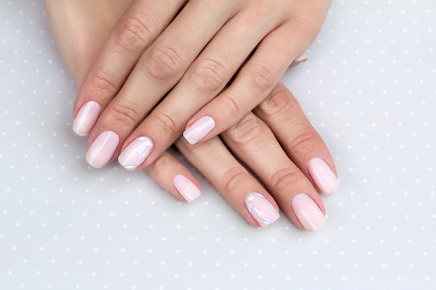 Piękne, zadbane dłonie kobiety z kobiecymi paznokciami na jasnoszarym stole.