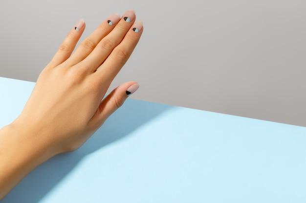 Piękne, zadbane dłonie kobiety z matowym wzorem w kolorze nude i niebieskim. koncepcja gabinetu kosmetycznego pedicure manicure.