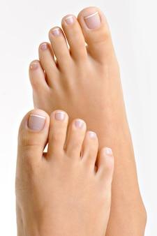 Piękne, zadbane kobiece stopy z francuskim pedicure. na białym tle.