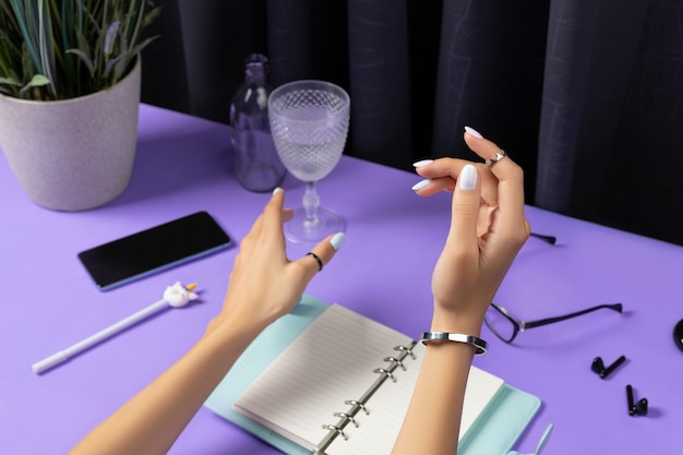 Piękne zadbane kobiety ręce nad fioletowym stołem. akcesoria damskie letnie