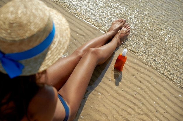 Piękne, zadbane nogi kobiety z kremem chroniącym przed poparzeniem słonecznym