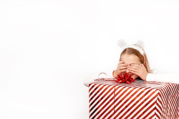 Piękne, zaskoczone dziecko dziewczyna trzyma pudełko świąteczne czerwone paski ze wstążką i kokardą w dłoniach.