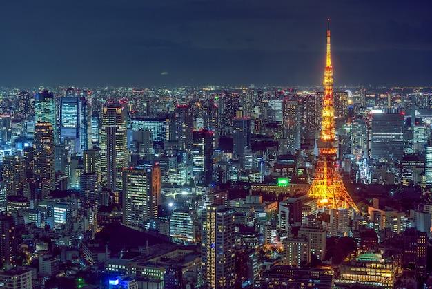 Piękne zdjęcia lotnicze nowoczesnej architektury miasta z oświetloną wieżą z boku