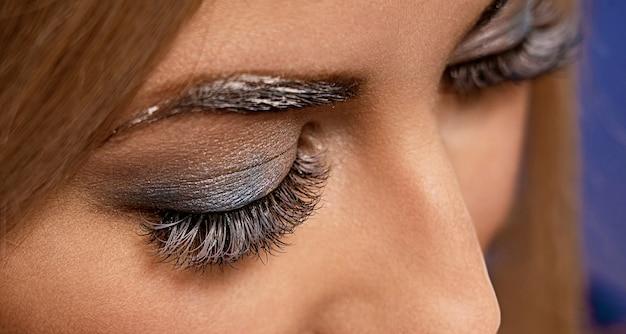 Piękne zdjęcia makro kobiecego oka z ekstremalnie długimi rzęsami i makijażem z czarnej liniowej