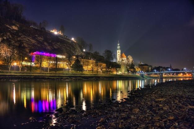 Piękne zdjęcie historycznego miasta salzburga odbijającego się w rzece w nocy