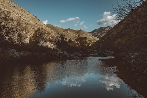 Piękne zdjęcie jeziora między wysokimi górami i wzgórzami