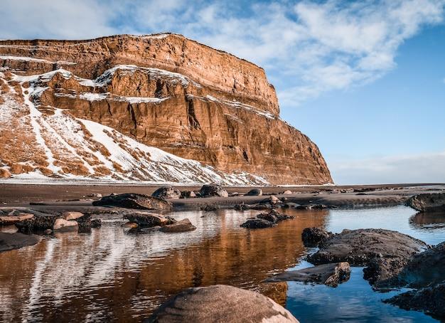 Piękne zdjęcie jeziora przed zaśnieżoną górą z niebieskim niebem