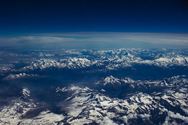 Piękne zdjęcie lotnicze śnieżnej, górskiej scenerii pod zapierającym dech w piersiach błękitnym niebem