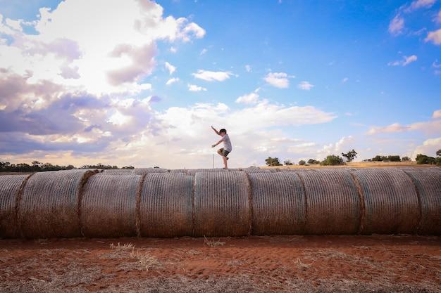 Piękne zdjęcie młodego chłopca balansującego na stosach siana