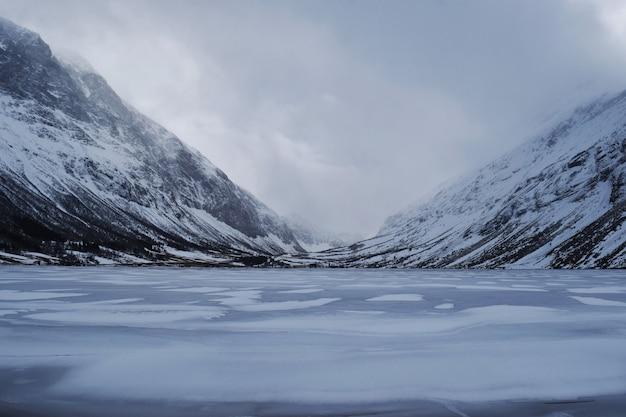 Piękne zdjęcie ośnieżonych gór w pobliżu zamarzniętego jeziora w norwegii
