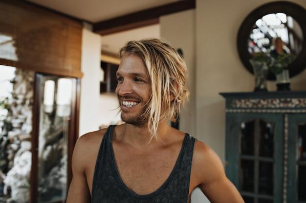Piękne zdjęcie portretowe młodego faceta z farbowanymi długimi włosami i śnieżnobiałym jasnym uśmiechem