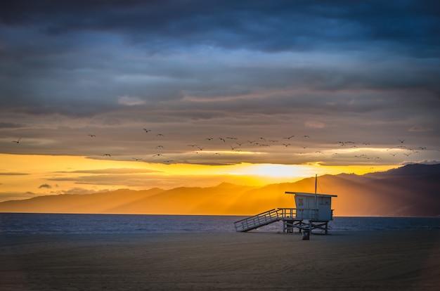 Piękne zdjęcie venice beach z górami w oddali pod zachmurzonym niebem o zachodzie słońca