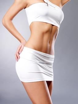 Piękne, zdrowe ciało kobiety w białych strojach sportowych